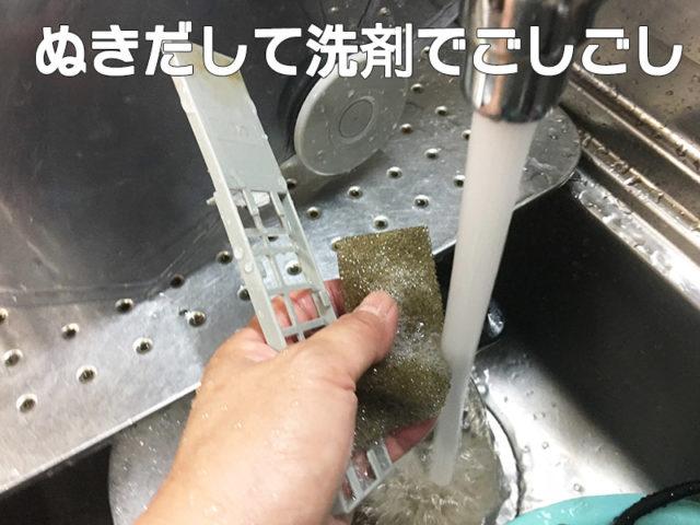 食器乾燥機をそうじしてたらエグいの出てきた!!【水垢どころじゃないよ】の乾燥機の裏の汚れたフィルターを洗っている画像